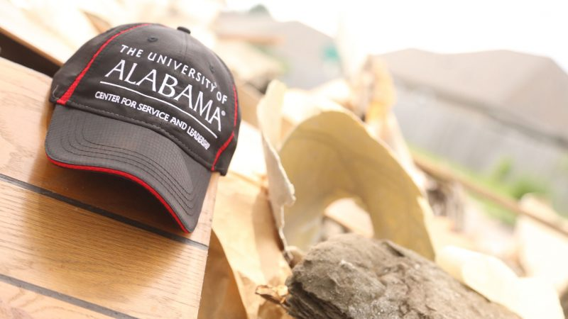 "a ball cap hat reading ""The University of Alabama Center for Service and Leadership"" sits on top of a pile of debris at a volunteer work site."