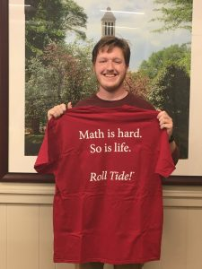 """young man holds up a red t-shirt that reads, """"Math is hard. So is life. Roll tide!"""""""