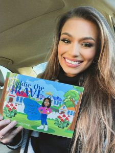 """young women holds up a children's book titled """"Maddie the Brave"""""""