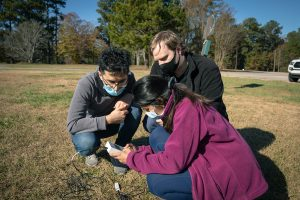 Three people gather around a sensor placed in the ground as part of scientific research.