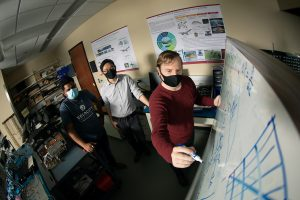 Three men with masks on gather around a white board with scientific schematics.
