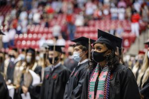 Students sit socially distant, wearing masks at commencement.