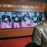 A bust of Paul Bryant in front of a digital display in the Bryant Museum