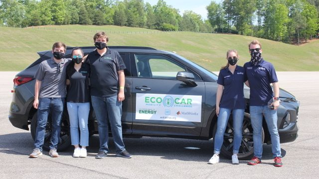 five students wearing masks pose next to a gray mid-size SUV