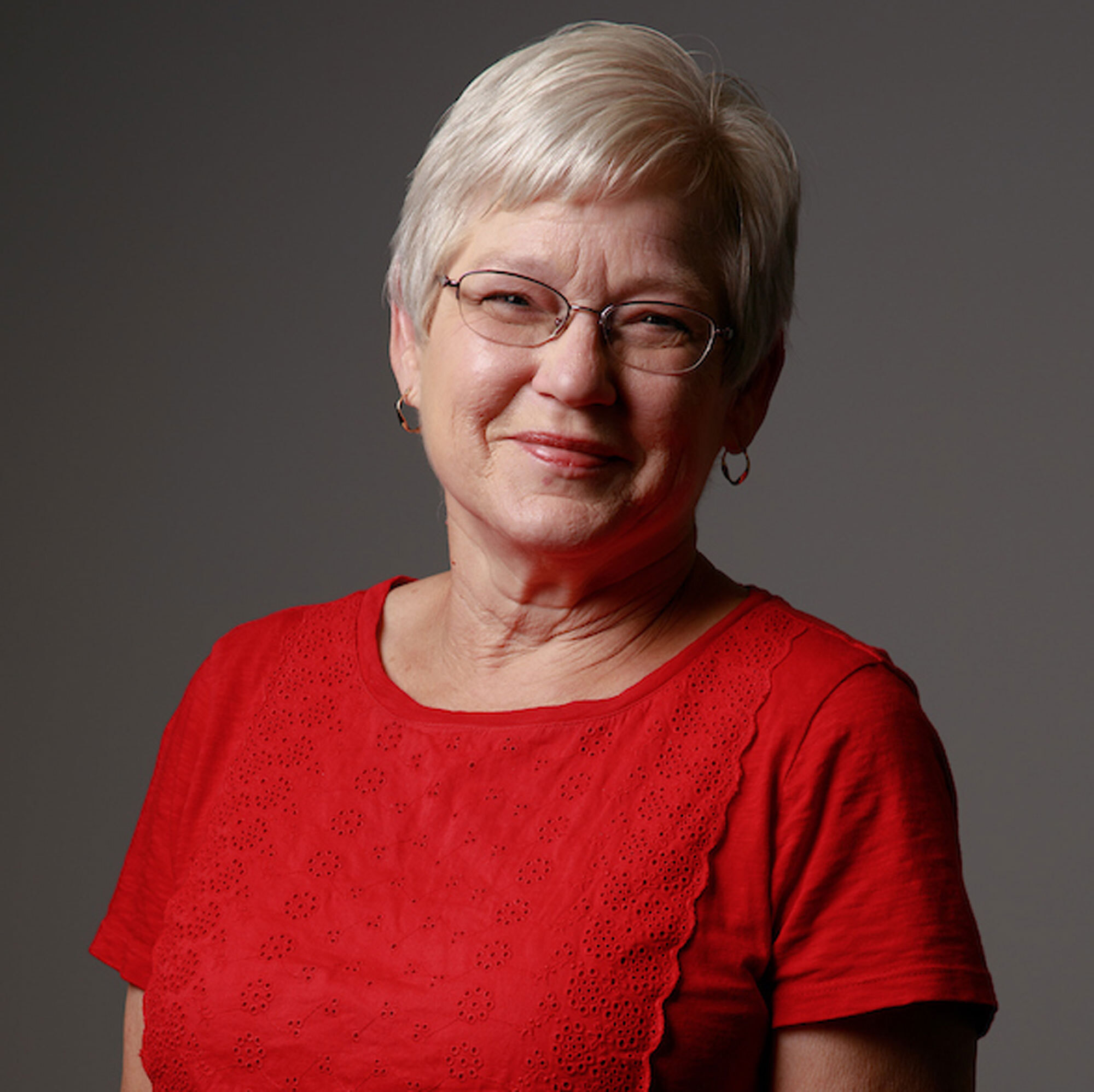 Jeannie Brooks smiles at the camera while wearing a crimson shirt