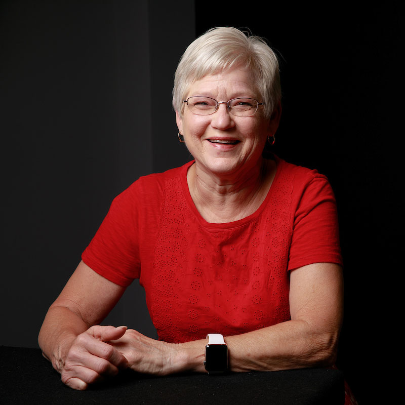 A woman wears a red shirt and is sitting while holding her hands. Jeanine Brooks is the director of UA's Action Card services.