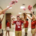 a line of avantis waving pom poms cheer while greeting a male bama bound attendee who smiles holding his fists in the air