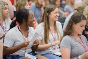 two young women smile while sitting in the audience at bama bound