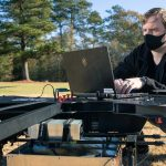 A man squats to type on a computer connected to a large drone in a field.