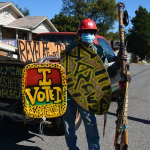 """Artist Joe Minter stands next to a truck wearing some of his art, including a colorful sign that reads """"I voted."""""""