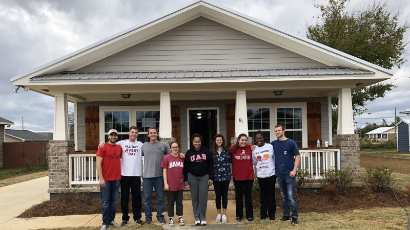UA Habitat for Humanity students standing in front of a completed home.