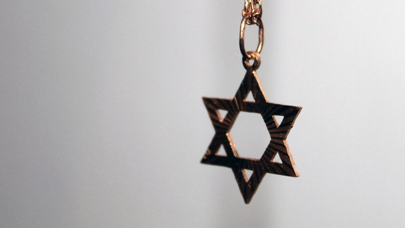 close up photograph of a gold star of david pendant