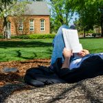 a female student leans against a tree on the quad while reading a book