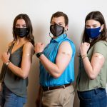 two female students and one male student stand wearing masks with their left arms flexing to show bandaids where they received the covid-19 vaccine