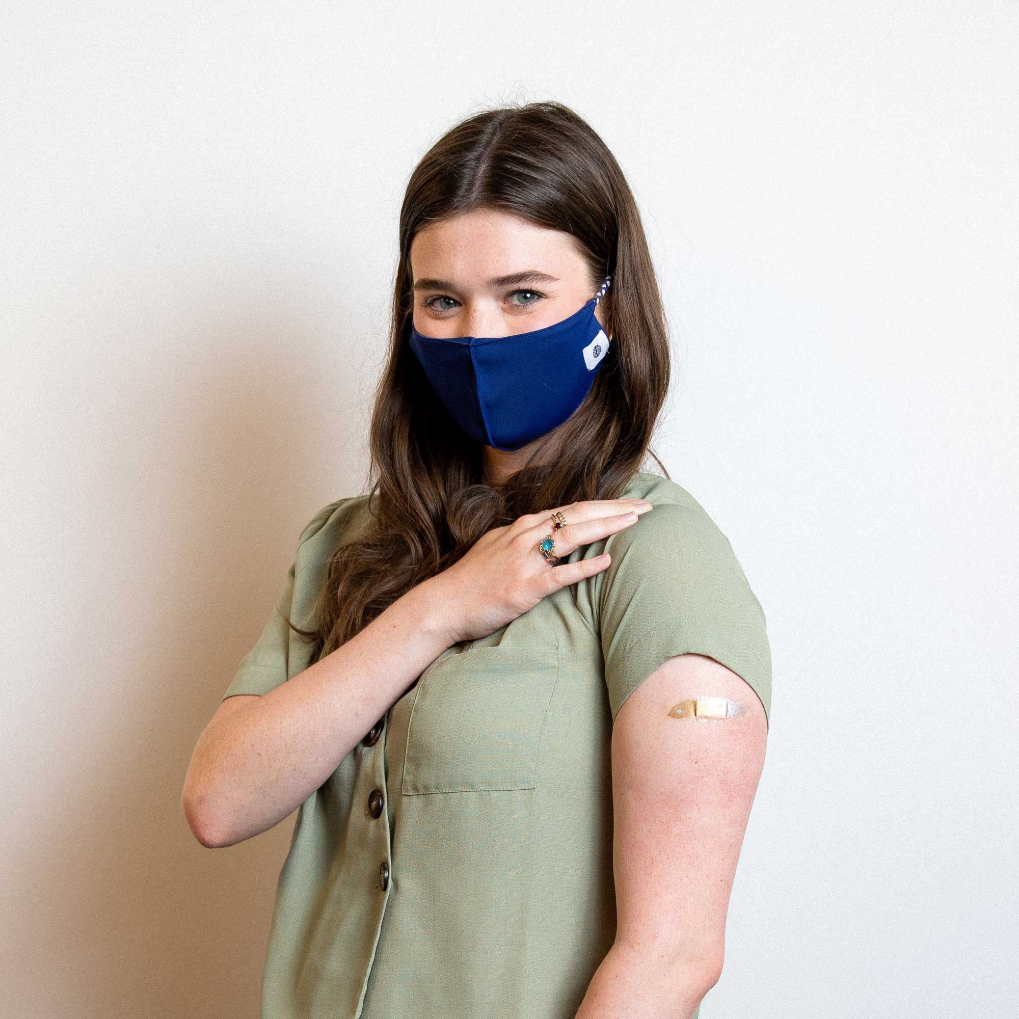 student wearing a mask with their sleeve rolled up to show a bandaid