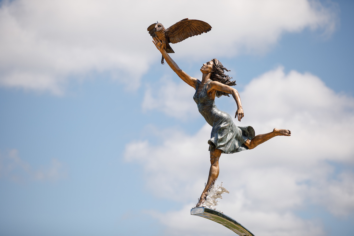 A bronze statue of a woman running with her right arm outreached to have an owl perch on it.