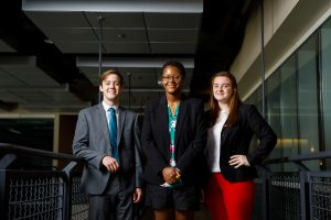 Three people pose for a photo inside a building at The University of Alabama.