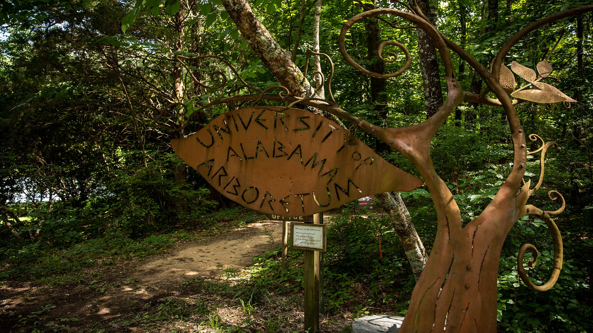 A sign says University of Alabama Arboretum out of metal.