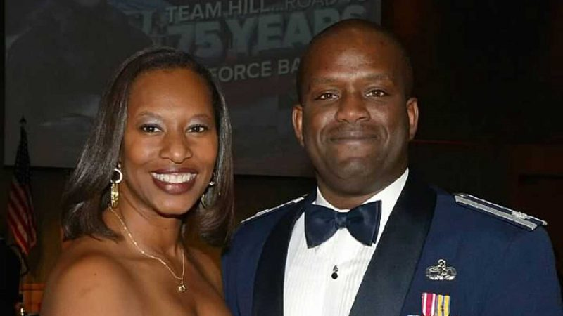 Smiling at the camera is a man and a woman, dressed in a military uniform and formal gown.