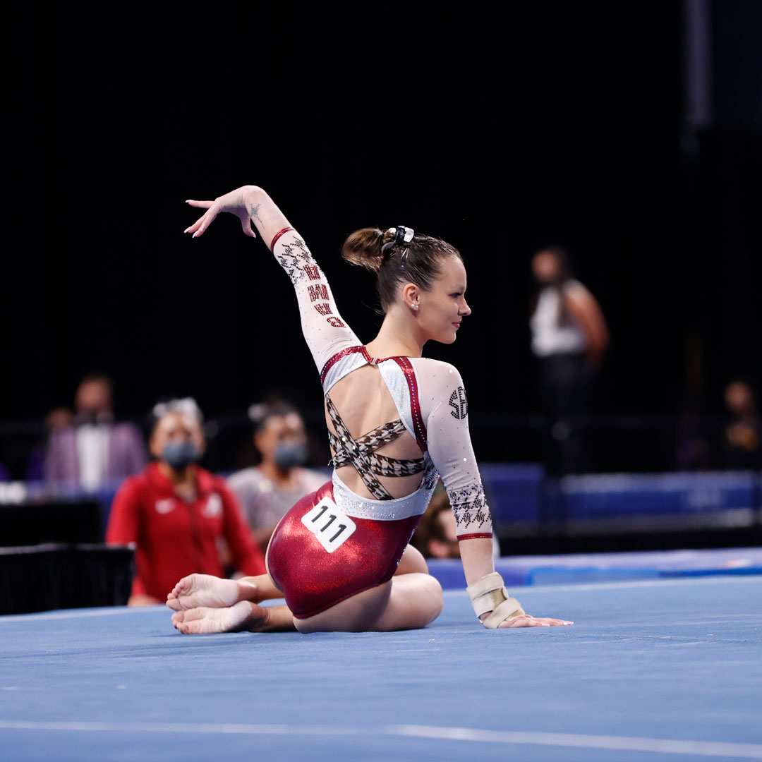 Sitting on a blue mat, a woman's legs are tucked under her body, with her left arm extended into a pose and her right hand propped up on the mat. The woman is in a crimson and white leotard.