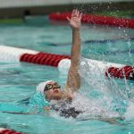 A woman is swimming the backstroke, with one arm getting ready to paddle. Crimson and white lane lines are also shown in the pool.