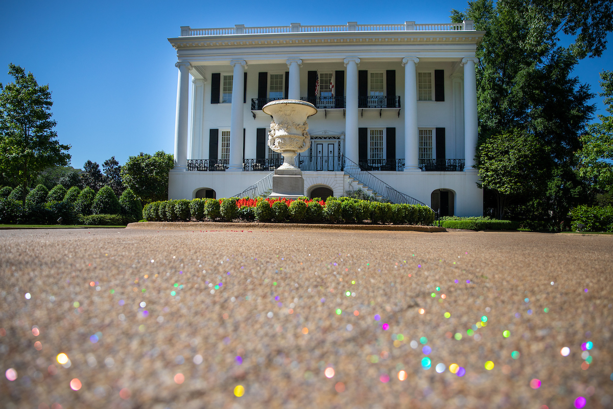 In the foreground, confetti of all colors is on the ground. A white Greek Rival styled house sits behind a statue of an urn.