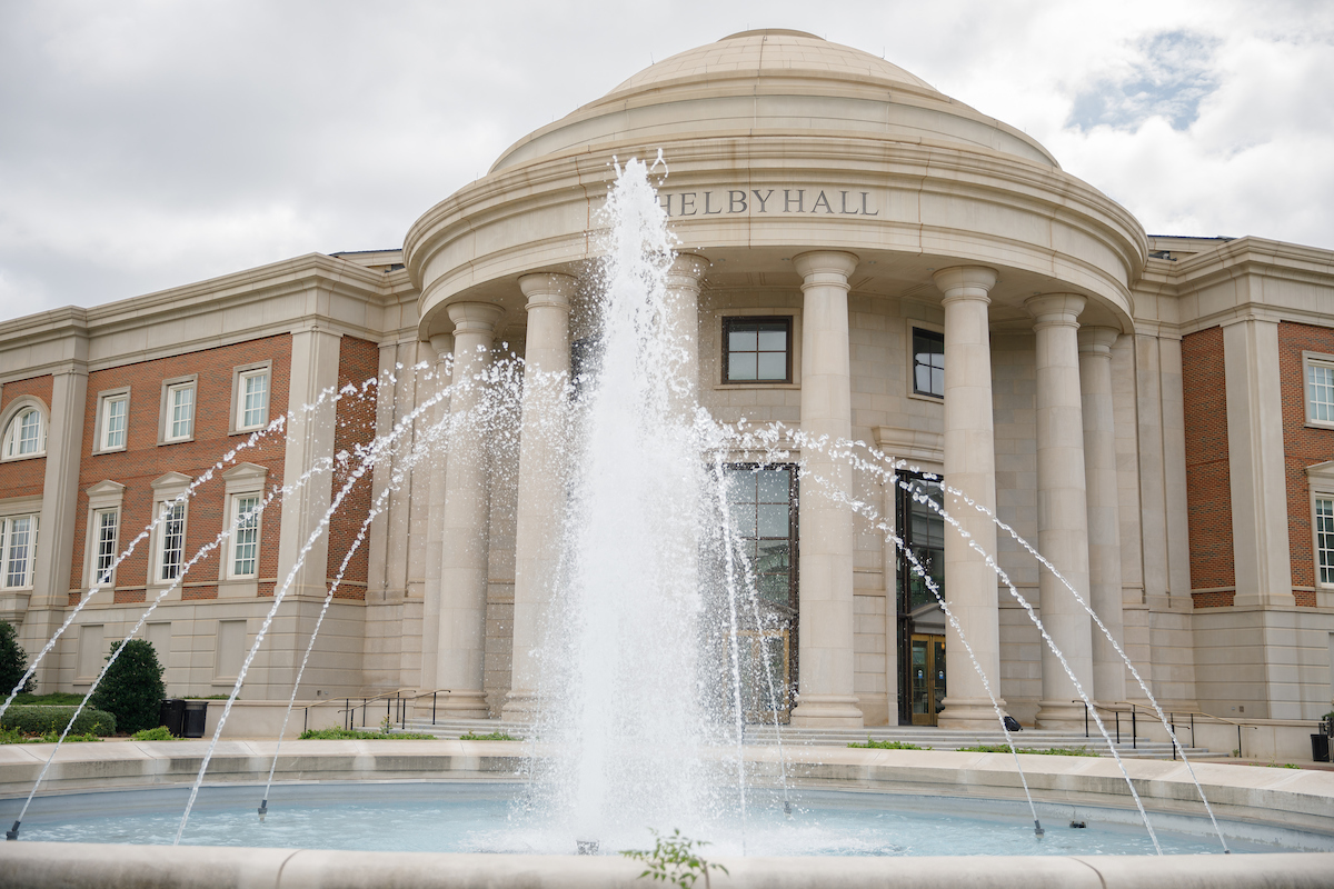 A fountain is spurting out water. The fountain is in front of a building.