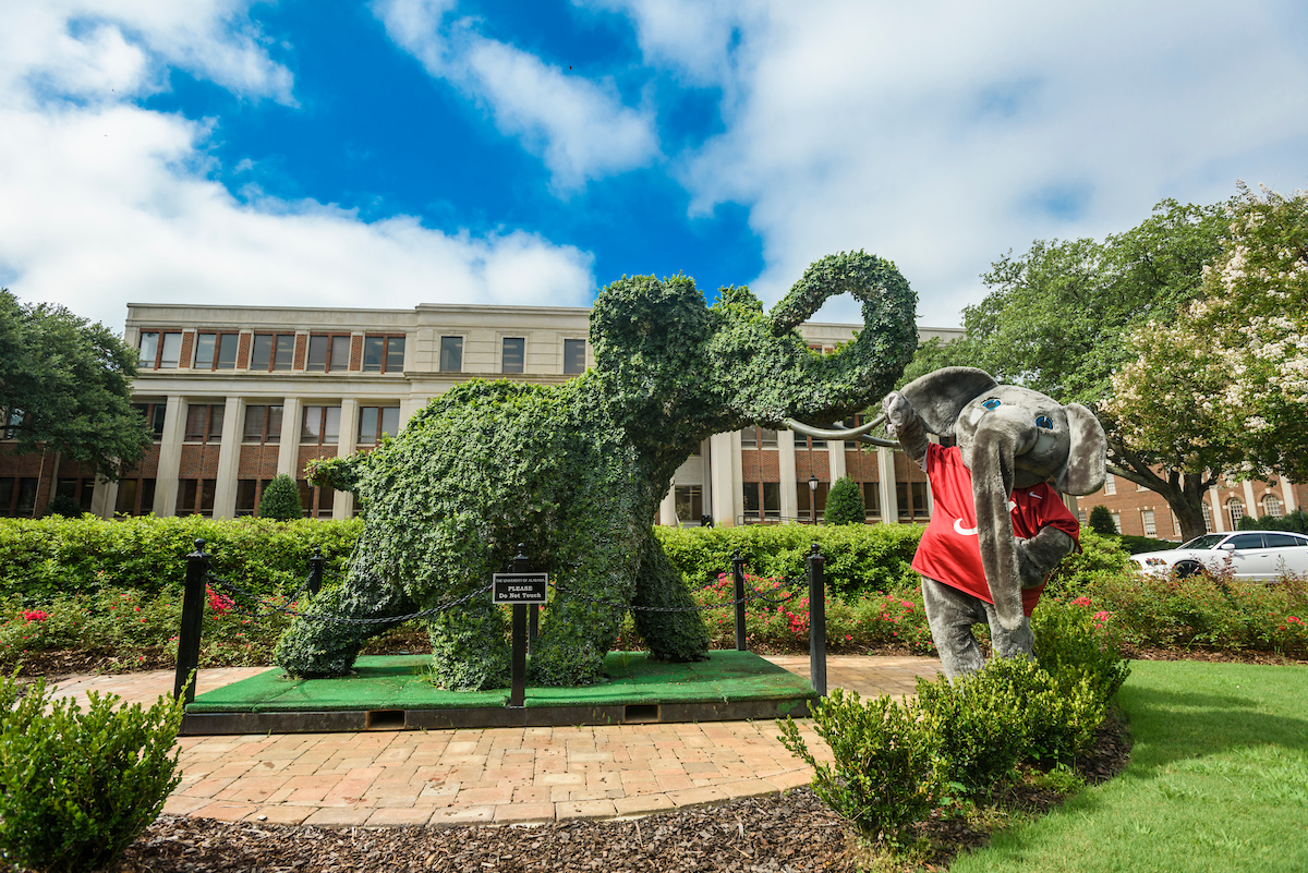 An elephant mascot stands next to a vibrant green elephant topiary.