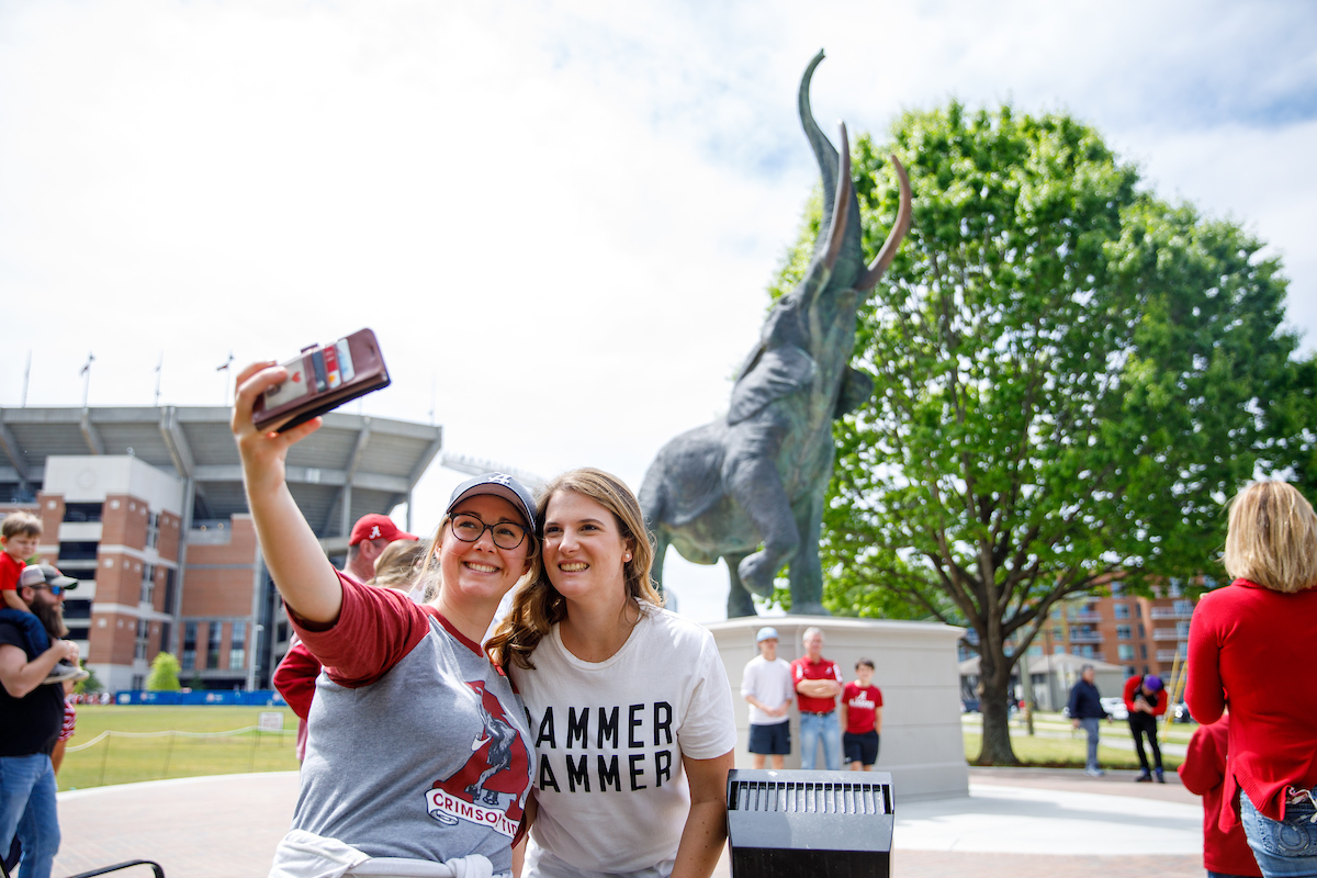 Two girls stand together taking a selfie with the bronze elephant statue, Tuska.