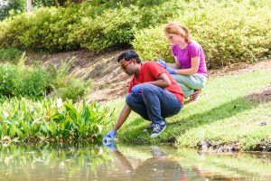 A student collecting a water sample from a pond while another student takes notes