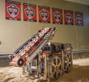A robot with four wheels and a conveyor belt for extraterrestrial digging against a wall that displays six NASA championship flags