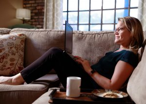 a woman sits on a couch with her feet up and her laptop in her lap