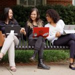 Three women sitting on a black bench outside are chatting. Each woman has a laptop.
