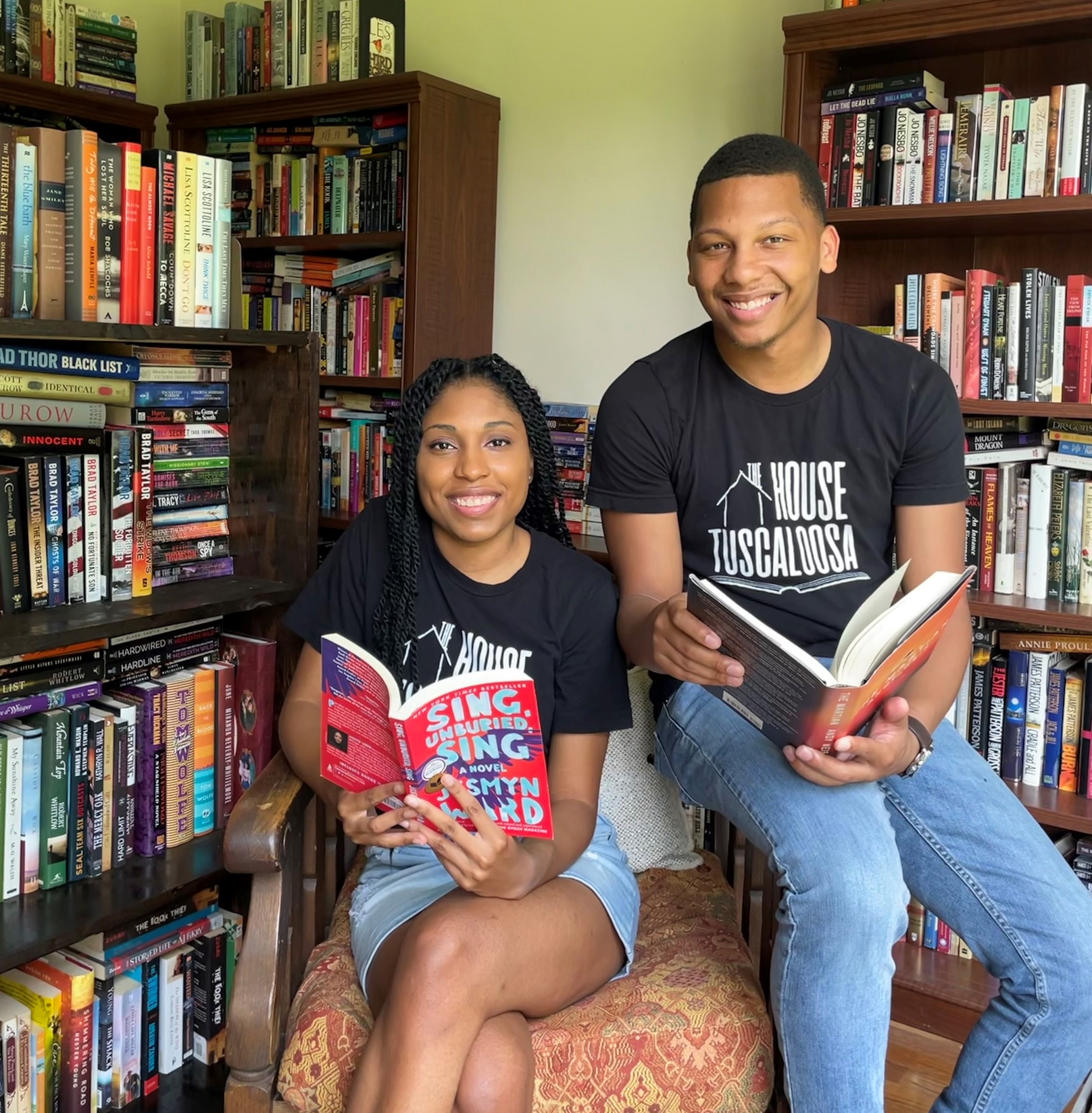 A woman and man post in front of bookshelves while sitting in a chair.