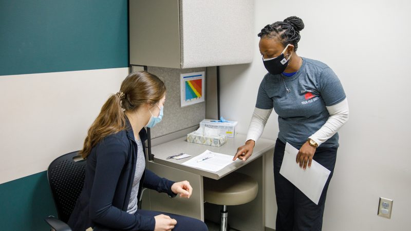 A nurse talking to a patient in a clinic exam room