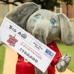 """Big Al holds a giant pledge card for the United Way that reads """"$400,000"""