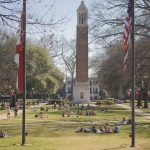 Photograph from the view of the steps of Gorgas Library looking out over the Quad full of groups of students sitting in the grass