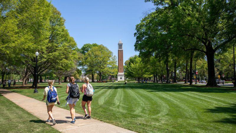 photograph of three students wearing backpacks and walking across the Quad on a clear, sunny day