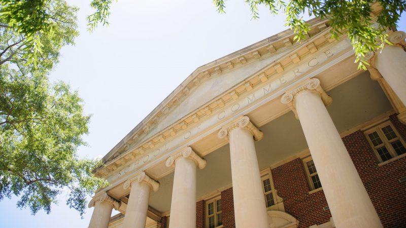 photograph of the exterior of a building with the words School of Commerce etched on the exterior