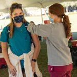 A student receiving a flu shot from a nursing student