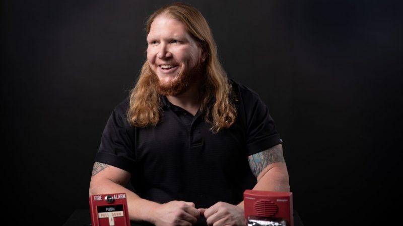 Caleb Hill, fire alarm technician at UA, sitting near two fire alarms