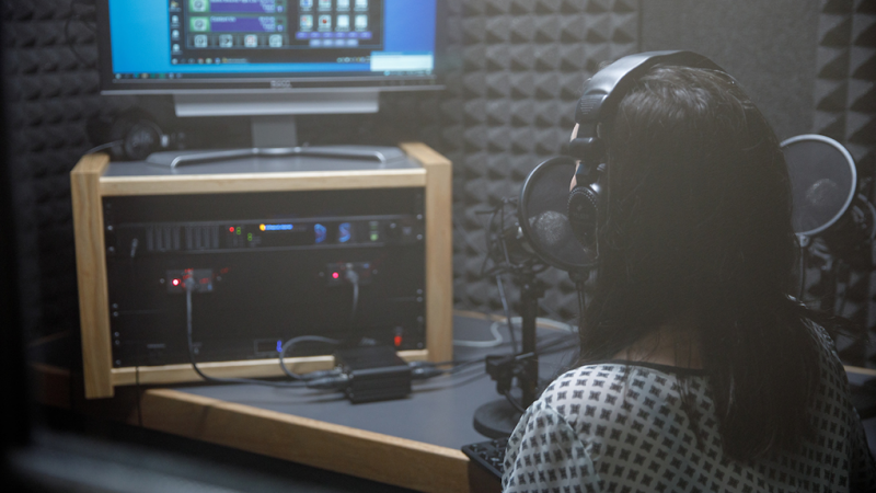 A woman talks into a microphone in a radio studio.