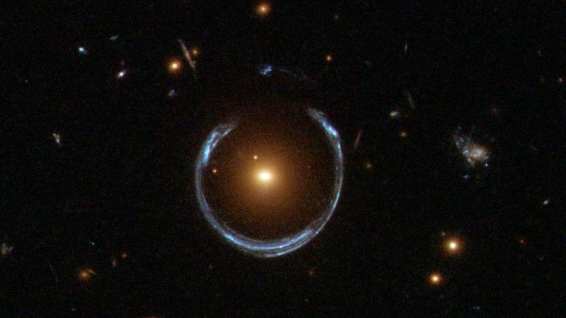 An image of space with a bright dot in the center surrounded by a blue horseshoe of light.