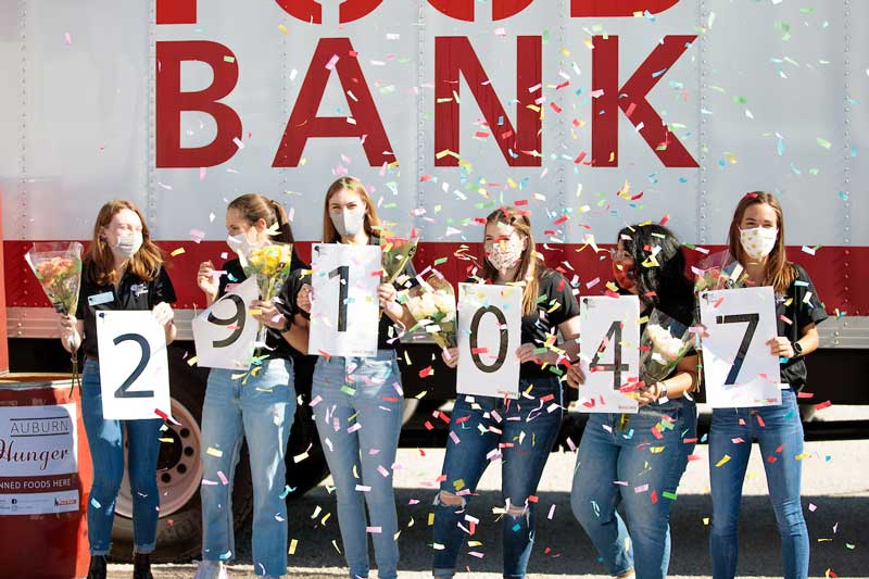 Six women stand in front of a semi-truck holding up the numbers 291047 which represents the pounds of food raised during the 2020 Beat Auburn Beat Hunger Food Drive.