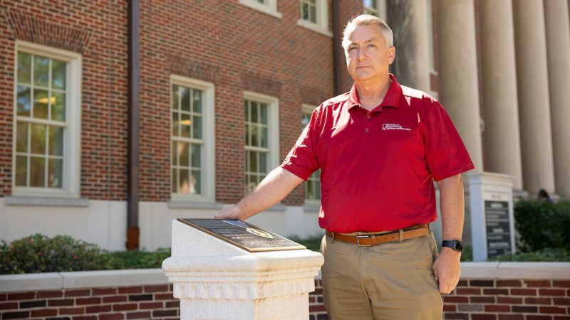 A man in a crimson shirt and khaki slacks stands next to a podium dedicated to Purple Heart recipients.
