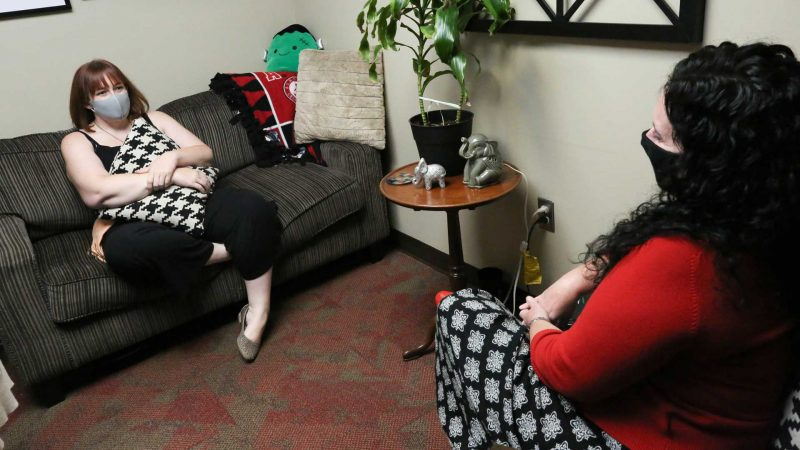 a woman sits on a couch talking to a counselor at the UA Counseling Center