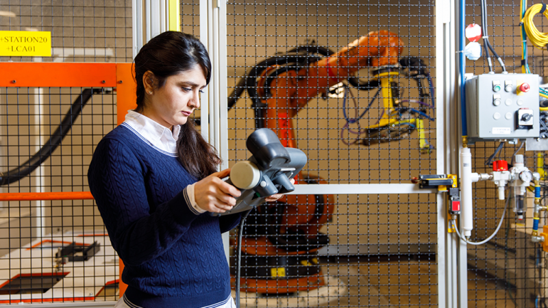 A student holds a controller for a robot that's in the background.