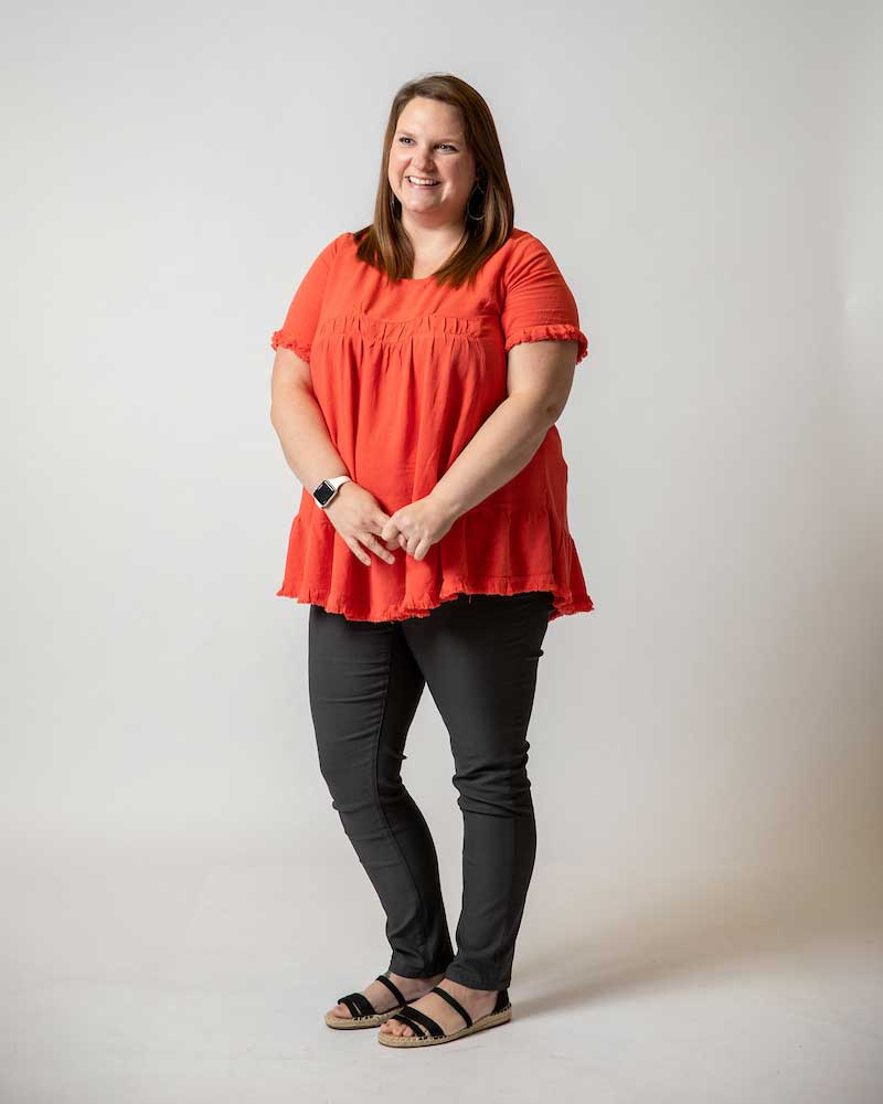 Standing in front of a white backdrop, a woman poses looking off-camera in a coral shirt, jeans and sandals.
