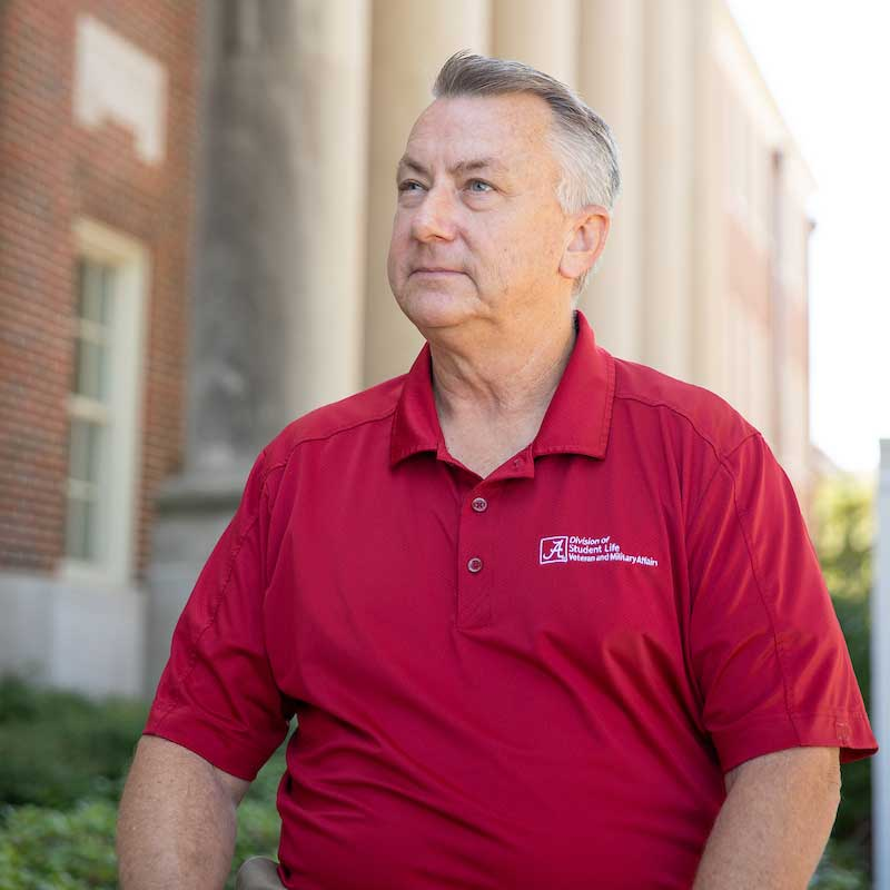 A man in a crimson shirt looks up and left towards the sky while standing outside.