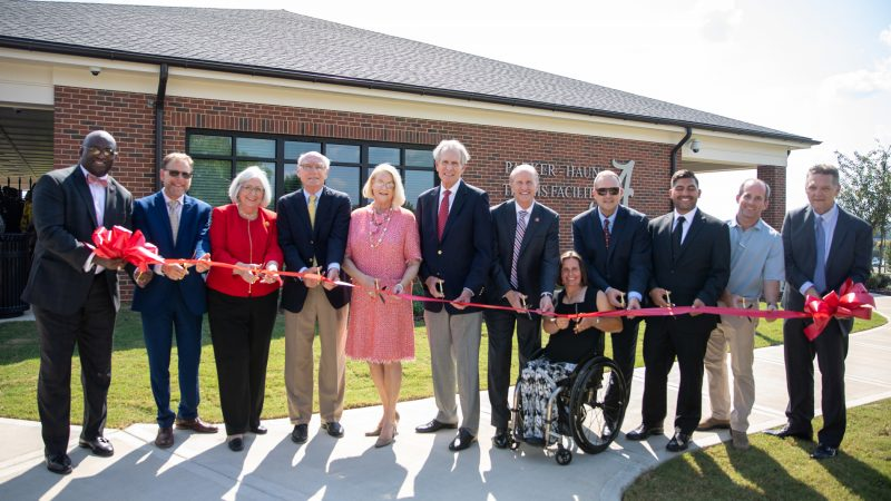 Several university representatives cutting the ribbon in front of the Parker-Haun Tennis Facility